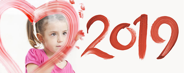 Blonde little girl painting with colors number new year 2019 on window