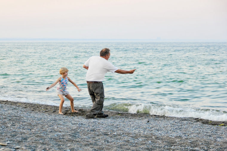 A young blonde girl at the lake shore on a pebble covered beach learning to skip rocks in the dusk from her grampa on the shores of Lake Ontario, Confederation Park Beach, Hamilton, Ontario, Canada.