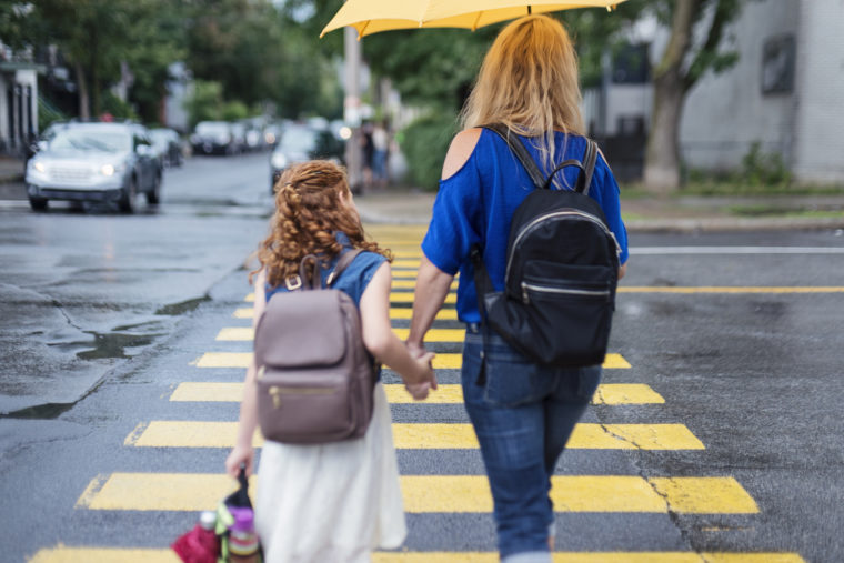 Young redhead girl and her single mother walking to school. Back view of them holding hands, crossing city street on rainy day. Horizontal waist up outdoors shot with copy space. This is part of a « Day in the life of a child » serie and was taken in Montreal, Canada.